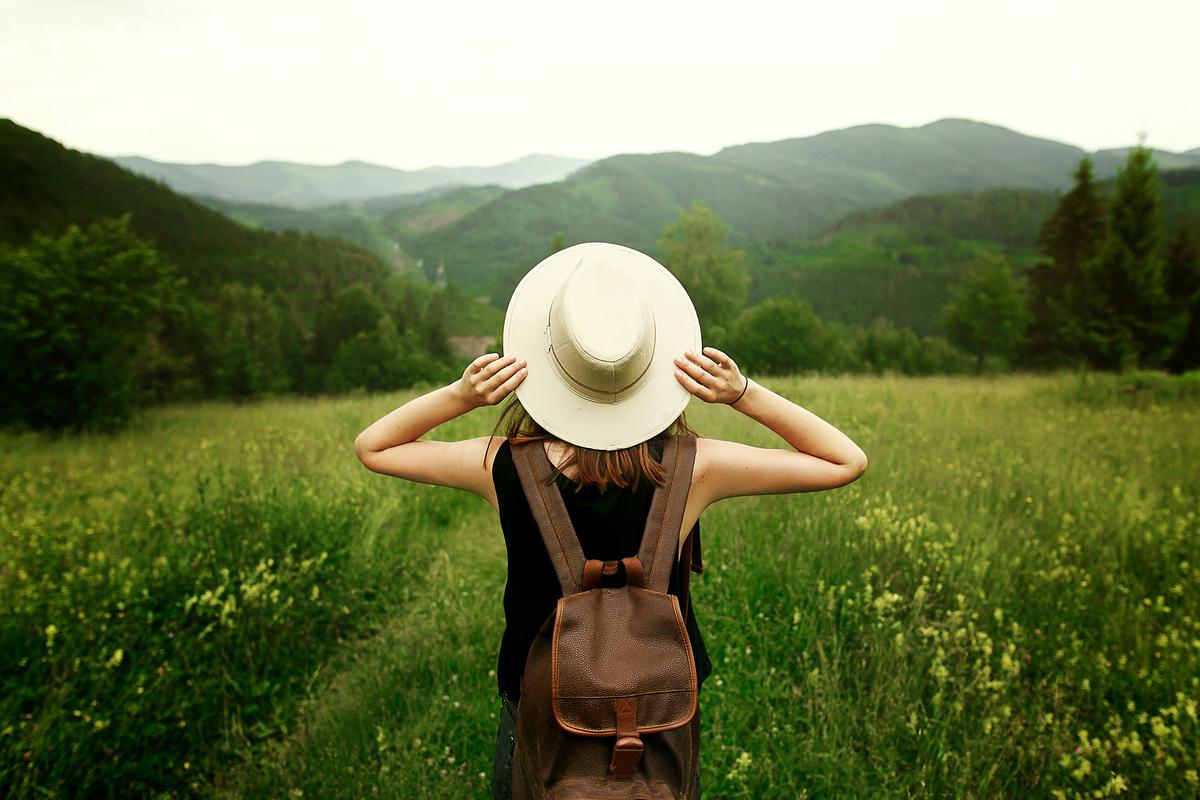 女性 帽子 草原 リュック 旅行